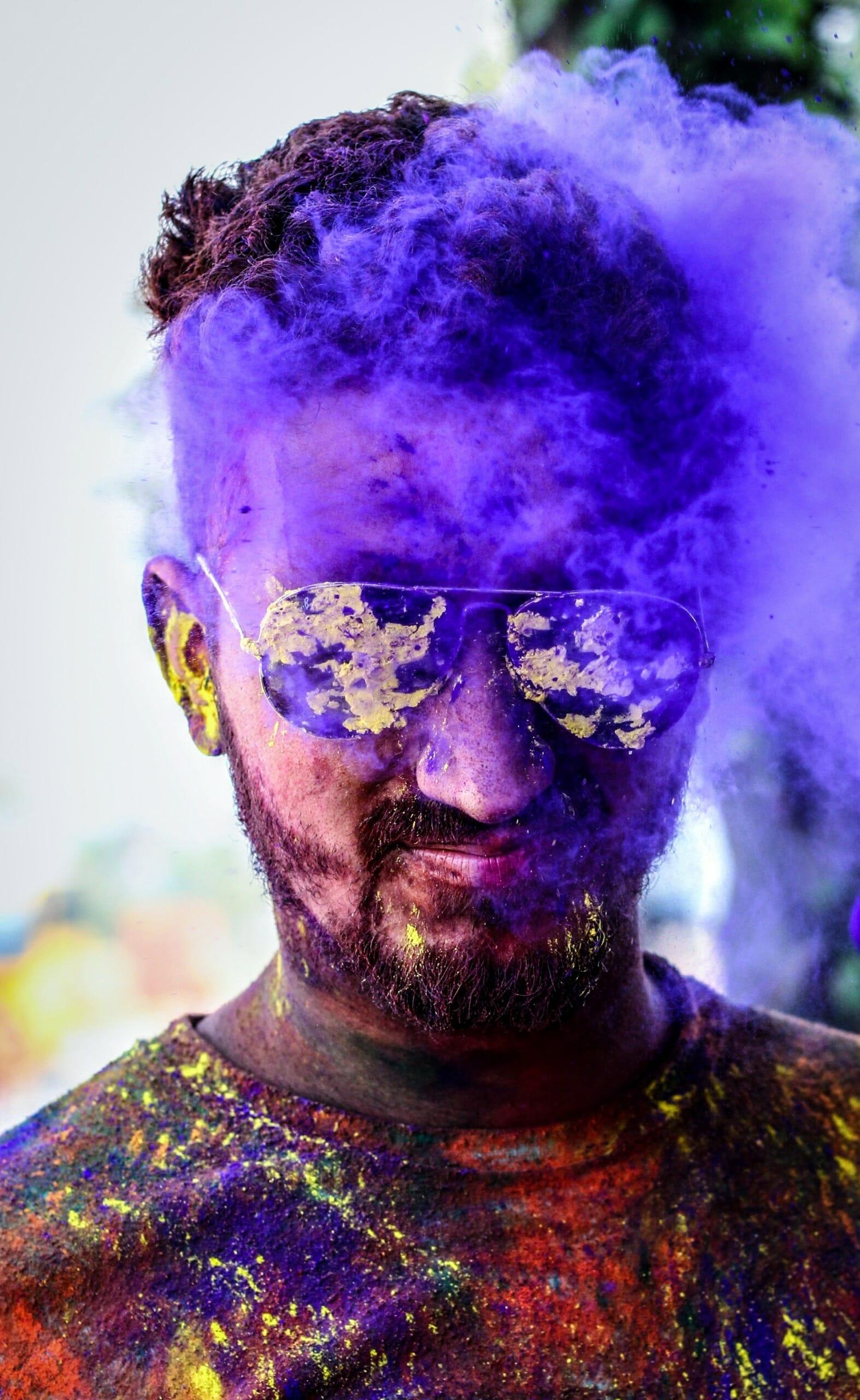 Stylish man in black aviator sunglasses with purple smoke