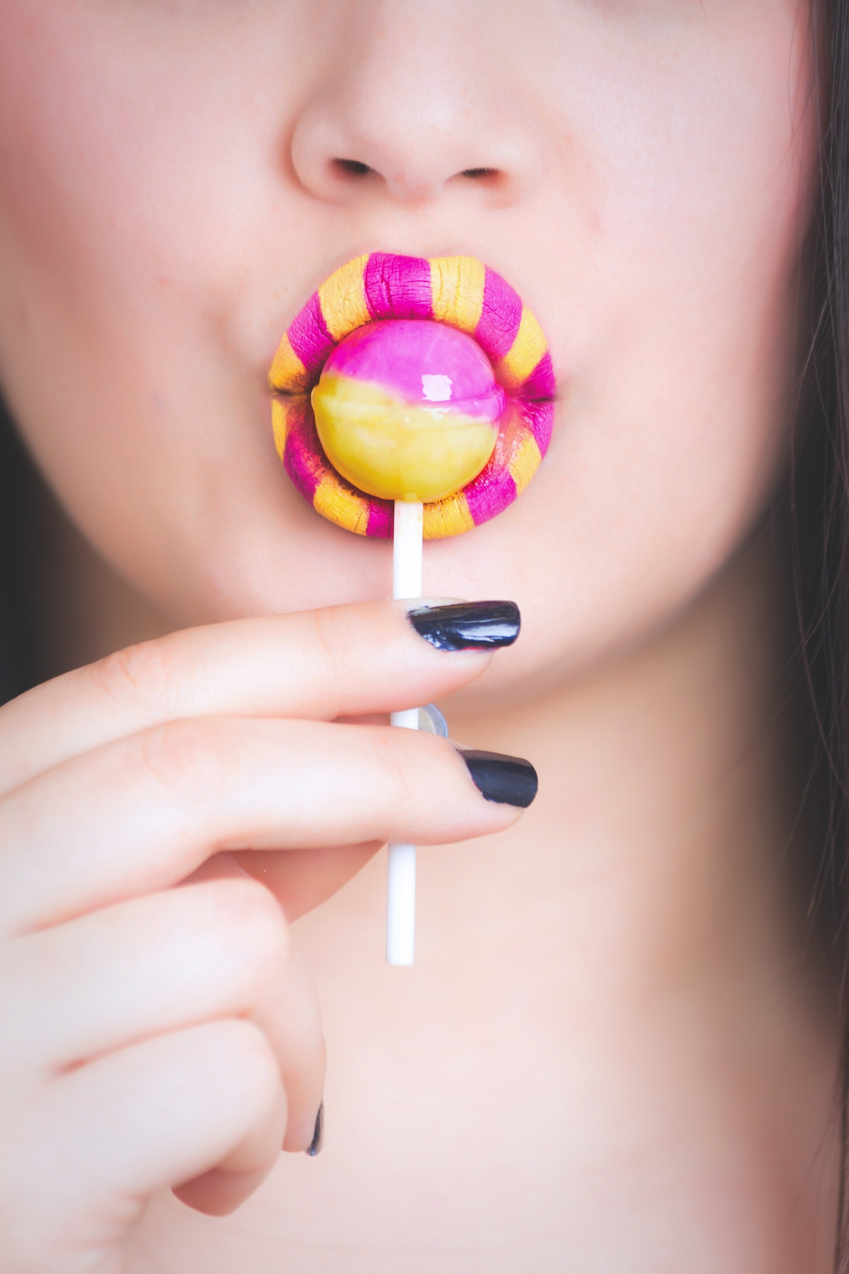 Woman Eating Pink and Yellow Lollipop